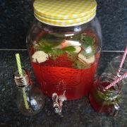 Glaskanister mit gelben Schraubverschluss mit selbstgemachtem Fruchtsaft, Trinklas mit Strohhalm aus alter Glühbirne und Trinkglas mit Henkel und rotem Strohhalm