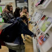 Jugendliche nehmen Informationsmaterial aus dem Regal