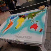 Weltkarte gespannt auf einem Tischtennis Tisch, im Hintergrund zwei Jugendliche