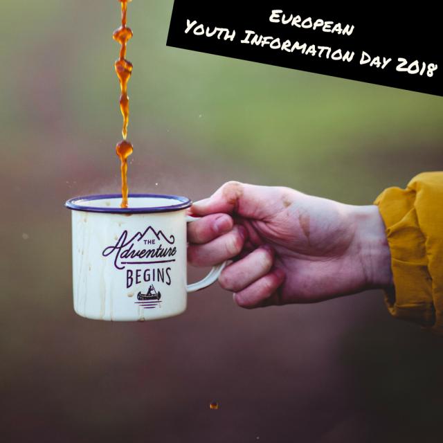 """Hand hält Tasse mit Aufschrift """"The Adventure begins"""" und Aufschrift """"European Youth Information Day"""""""