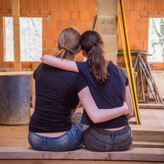 Zwei junge Frauen umarmen sich und schauen auf eine Baustelle