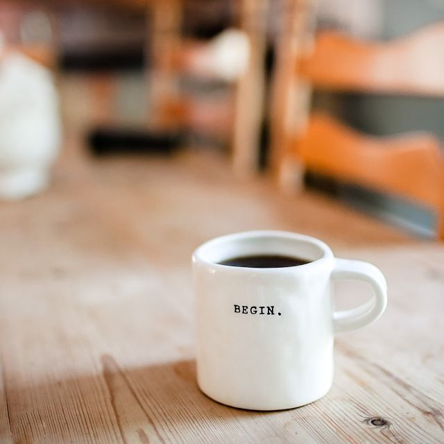 weiße Keramiktasse mit Kaffee auf einem Holztisch