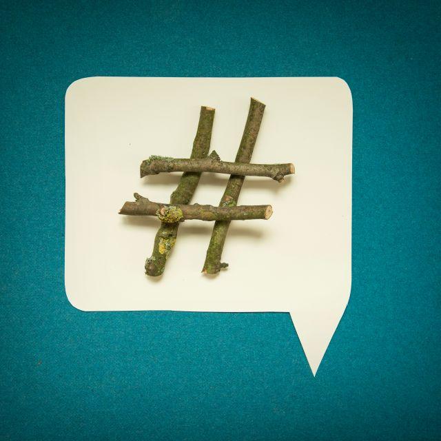 Hashtag aus Holz in blauer Sprechblase