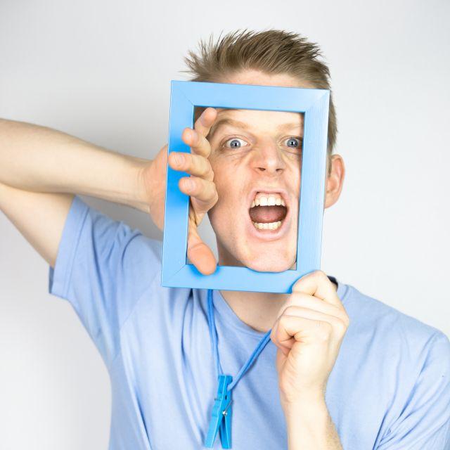 Junger Mann schneidet Grimasse und hält sich Bilderrahmen vor das Gesicht