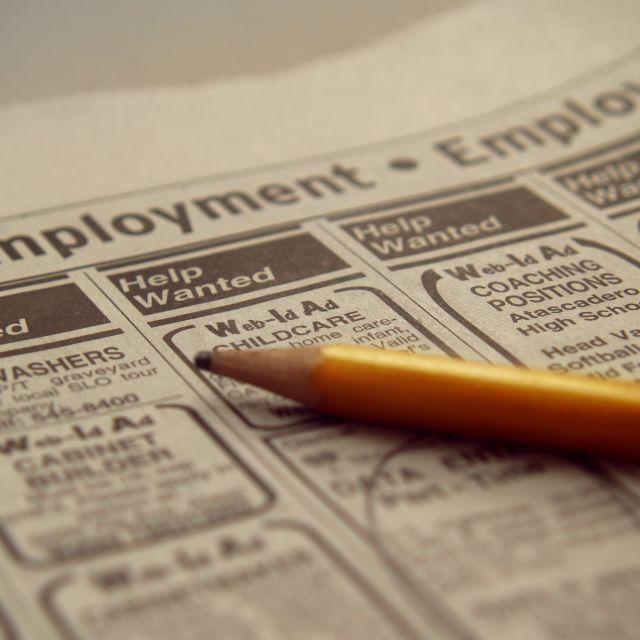 Gelber Bleistift auf Stellenanzeigen in der Zeitung