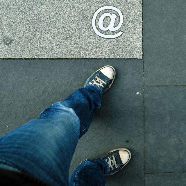 Internet-Zeichen auf Betonplatte, Beine in Jeans und Converse stehen auf der Platte