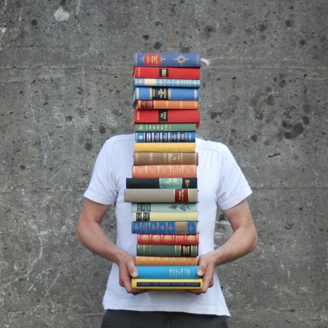 Jugendlicher hält riesigen Bücherstapel