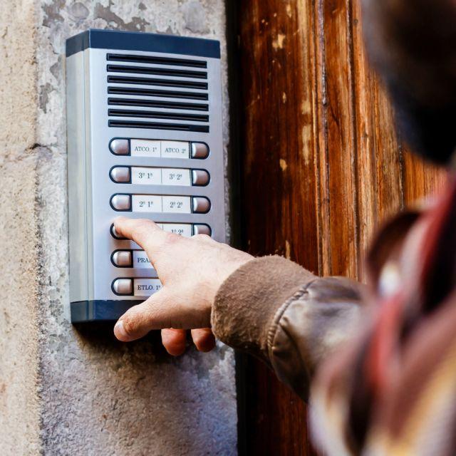 Gegensprechanlage und Hand, die auf einen Knopf drückt