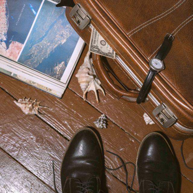 brauner Fußboden, zwei paar Schuhe, Koffer, Dollarschein