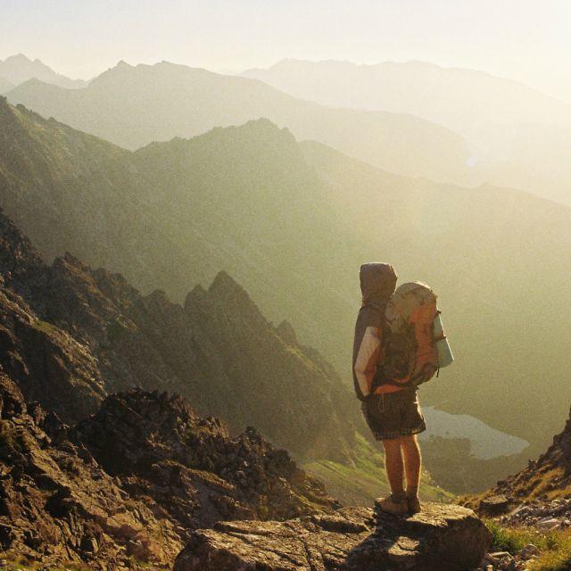 Junge Person mit Rucksack in den Bergen