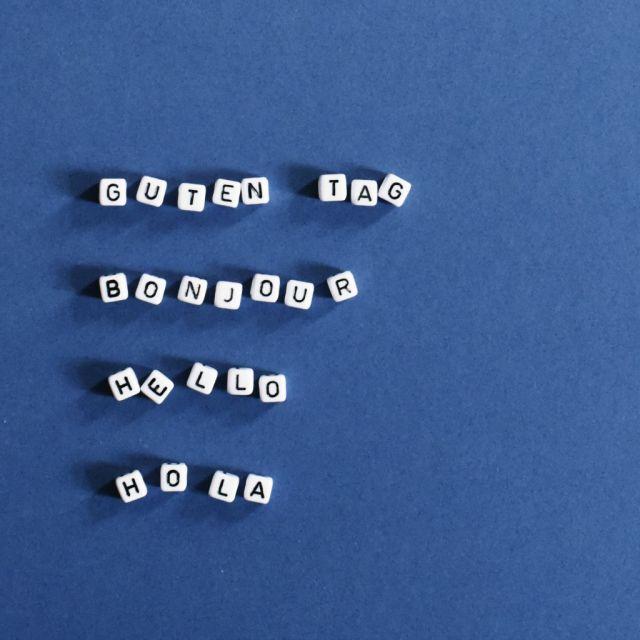 Blauer Hintergrund, Buchstaben mit Guten Tag, Bonjour, Hello, Hola