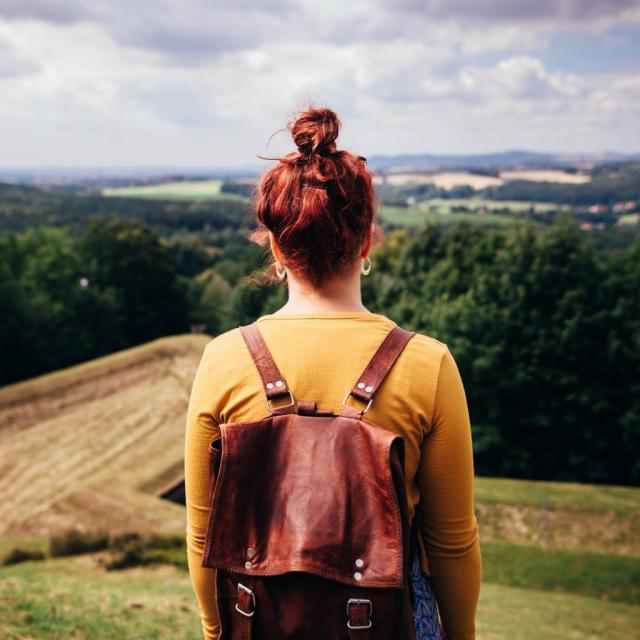 Mädchen mit Rucksack vor Landschaft