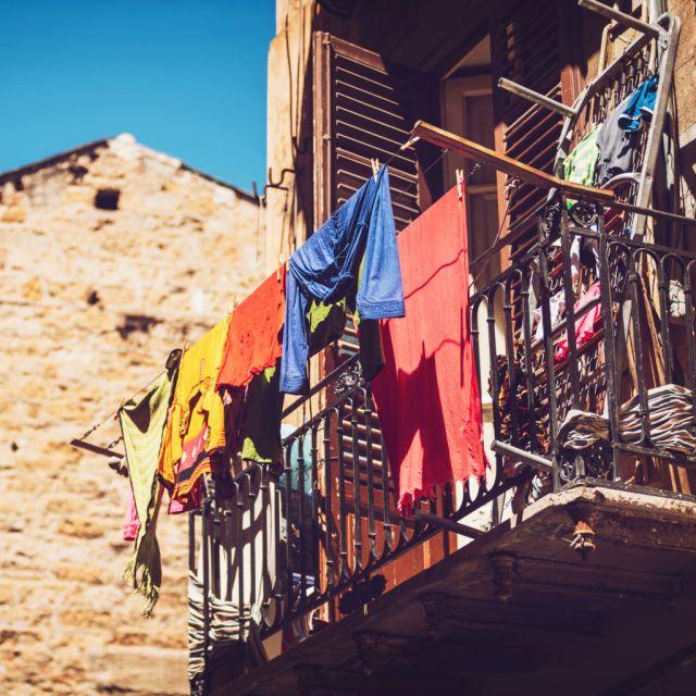 Balkon mit bunter Wäsche zum Trocknen, blauer Himmel