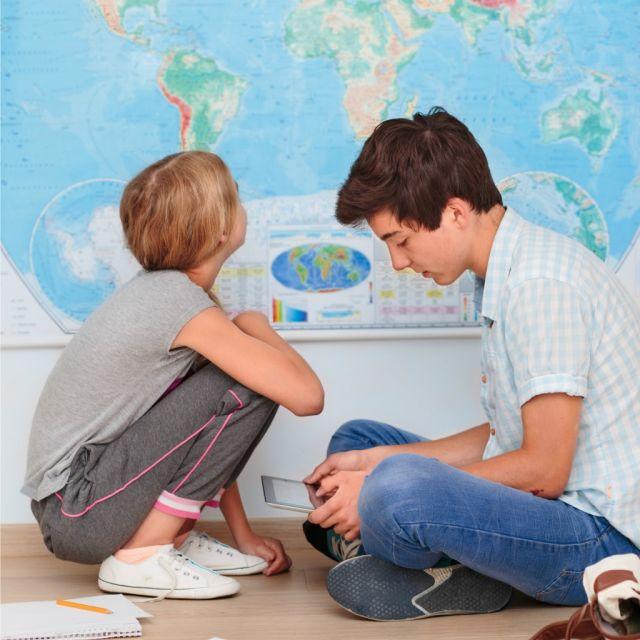Ein Mädchen und ein Junge vor einer Weltkarte
