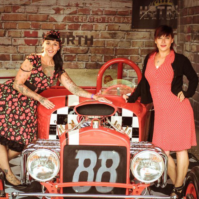 Zwei Frauen im 50iger Jahre Stil gekleidet stehen neben einem Oldtimer