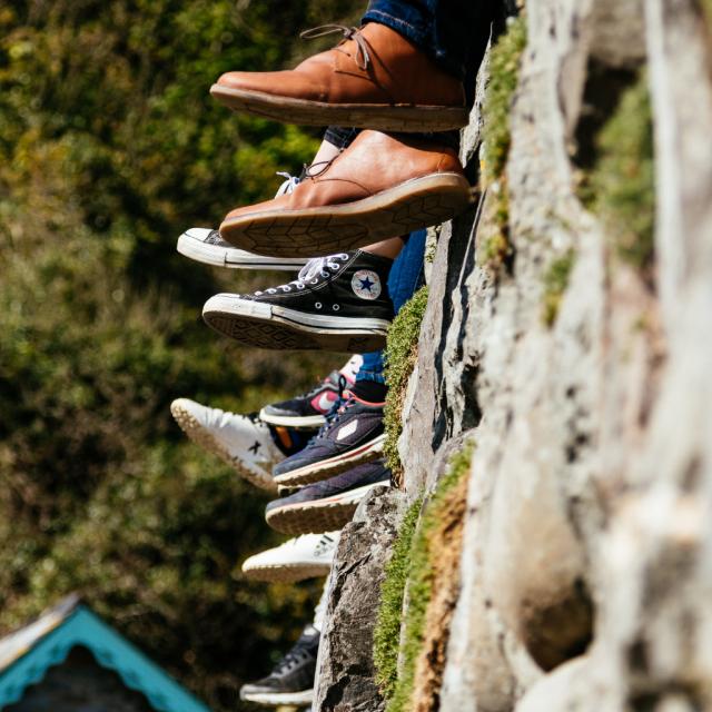 Wald und Felsen, Füße mit verschiedenen Schuhen, im Hintergrund der Giebel eines Hauses