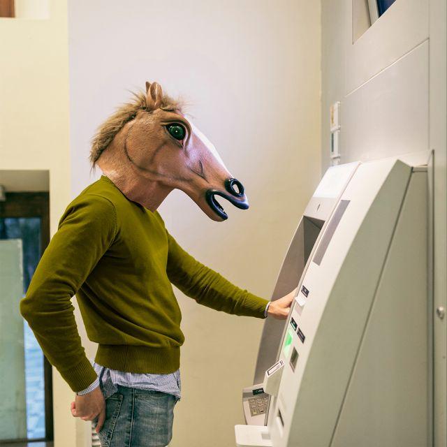 Flyer Sujet Jobbörse Mann mit Pferdemaske in grünem Pulllover steht vor Bankomat