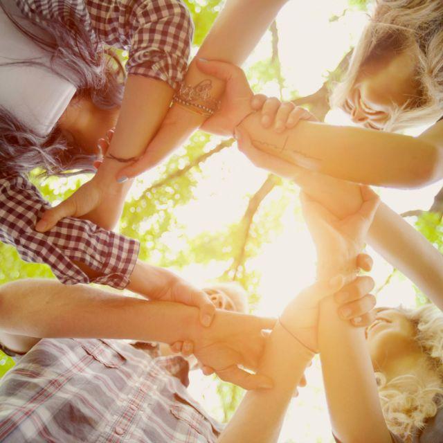 Vier Jugendliche von unten fotografiert, die sich die Hände reichen