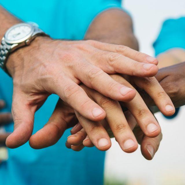 viele Hände übereinander freundschaftlich