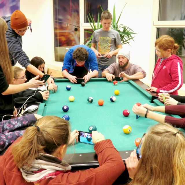 Billardtisch mit Jugendlichen rundherum
