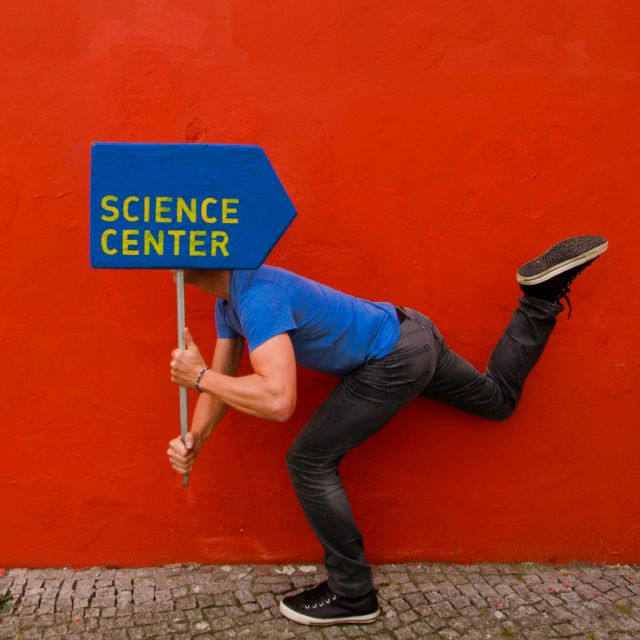 Mann mit Schild Science Center