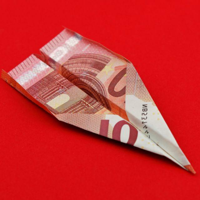 roter Hintergrund, Papierflieger gefaltet aus einem Zehneuroschein