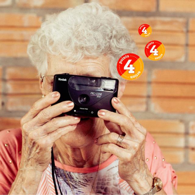 Alte Frau mit Kamera vor dem Gesicht - Points, die als Blitz aus der Kamera kommen.