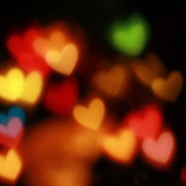Bunte, leuchtende Herzen auf schwarzem Hintergrund