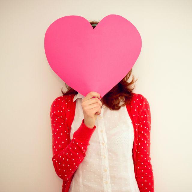 Mädchen mit rosa Herz aus Papier vor dem Gesicht