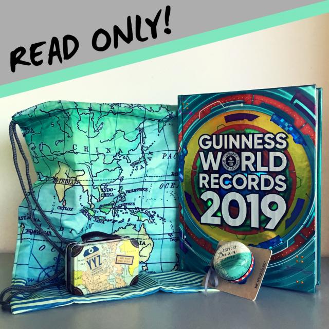 Buchcover Guinness World Records 2019 und Fahrradklingel, Turnbeutel und kleiner Reisekoffer im Reisedesign