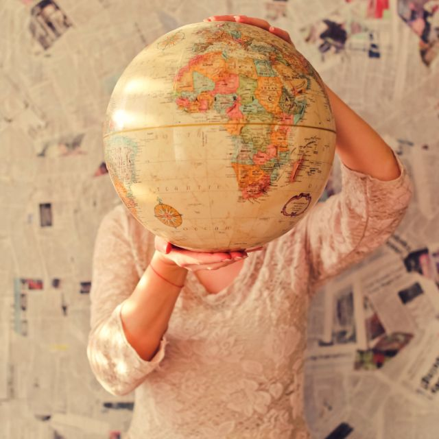 Mädchen mit Globus vor dem Gesicht