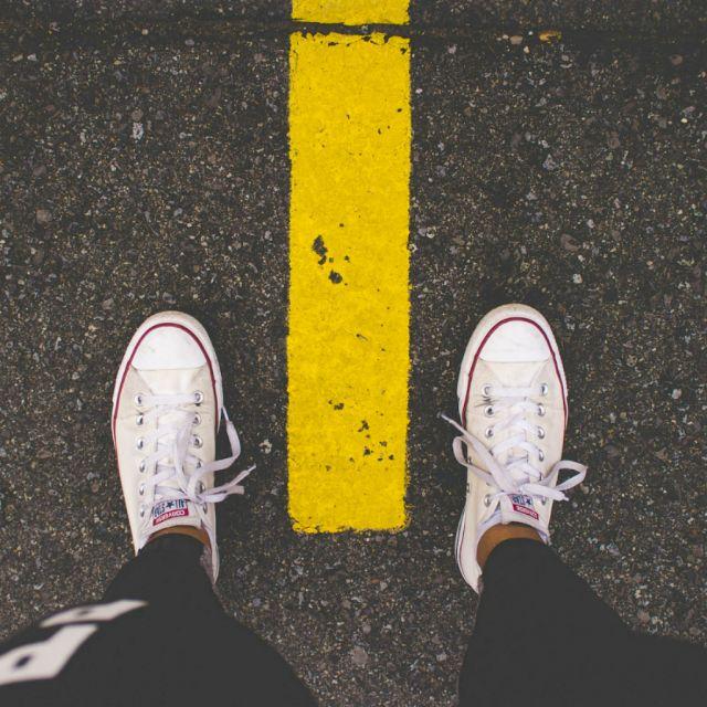 Füße mit Turnschuhen von oben fotografiert