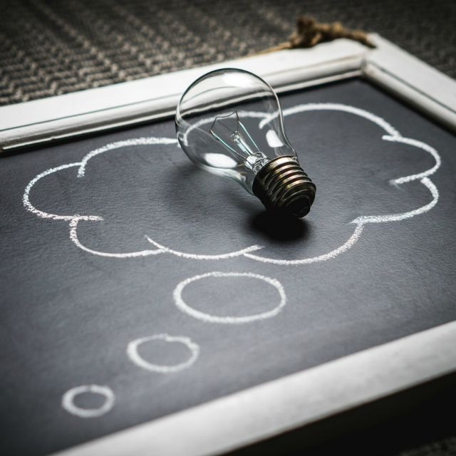 Tafel mit gezeichneter Gedankenblase. Darauf liegt eine Glühbirne.