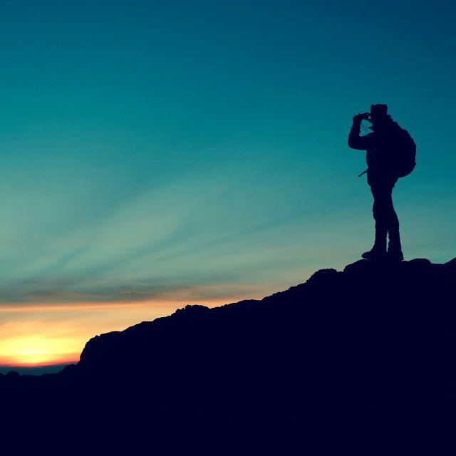 Junger Mensch betrachtet die Welt von einem Gipfel aus