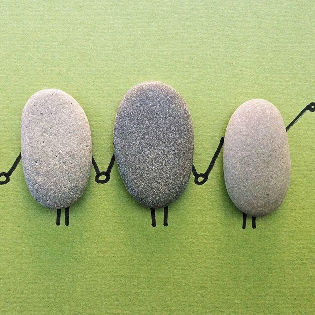 Steine mit Händen und Beinen, die sich die Hand geben.