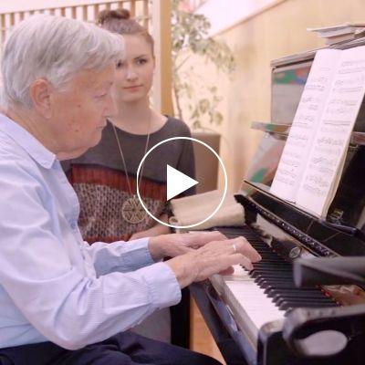 Senior spielt Klavier - Jugendliche sitzt daneben und hört zu